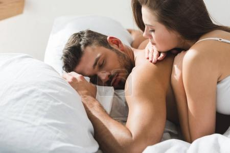 young woman lying on her sleeping boyfriend in morning