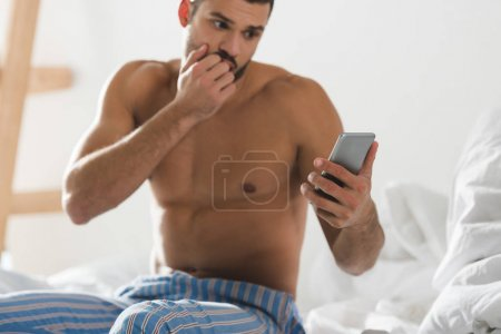 Photo for Shocked overslept man looking at smartphone in bed in morning - Royalty Free Image