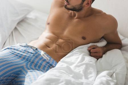 cropped shot of shirtless young man in pajamas pants lying in bed