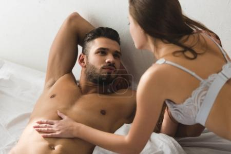 woman touching her shirtless boyfriend in bed in morning