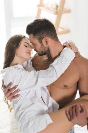 Photo pour Bel homme torse nu portant sa belle petite amie - image libre de droit