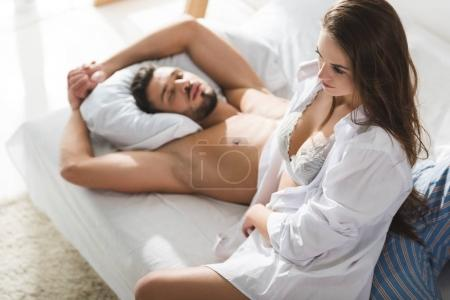 high angle view of beautiful young woman sitting near sleeping boyfriend in morning