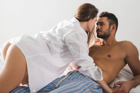 young passionate couple in bed at home