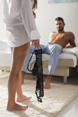 cropped shot of woman with bra in hand standing in front of boyfriend while he sitting on bed