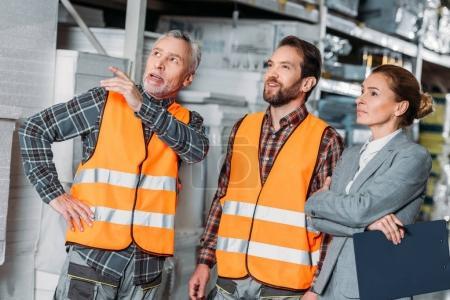 Photo pour Travailleurs montrant entrepôt à inspecteur femelle - image libre de droit