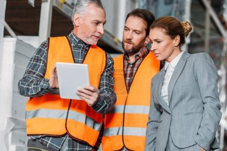 workers and inspector using digital tablet in storehouse