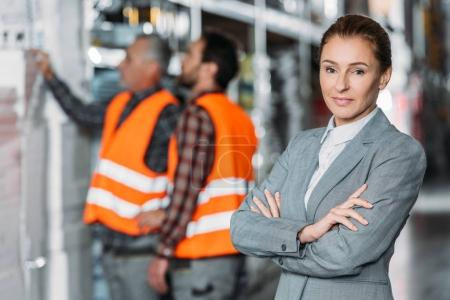 female inspector pising with crossed arms while men working behind in storehouse