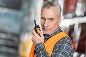 senior worker using walkie talkie in shipping stock