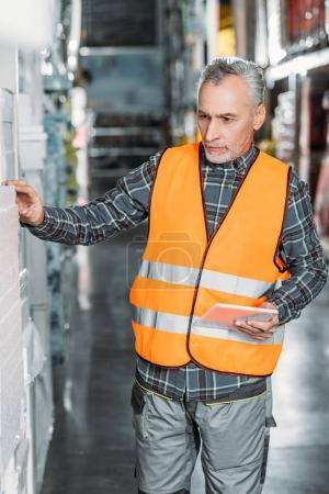 Photo pour Senior travailleur au gilet de sécurité à l'aide de tablette numérique dans l'entrepôt - image libre de droit