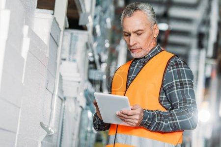 senior worker in safety vest using digital tablet in storehouse