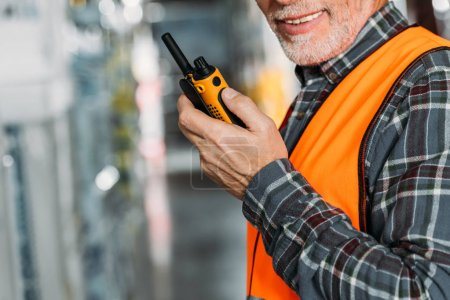 cropped view of senior worker using walkie talkie in storehouse