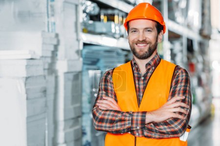 Photo for Smiling worker in helmet and safety vest with crossed arms in warehouse - Royalty Free Image