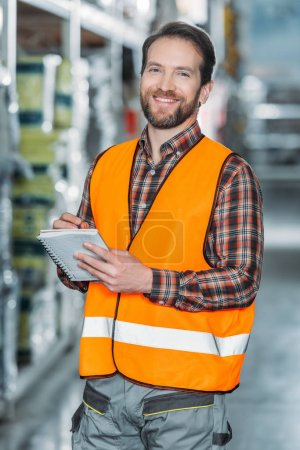 smiling worker in safety vest writing in notepad in storehouse