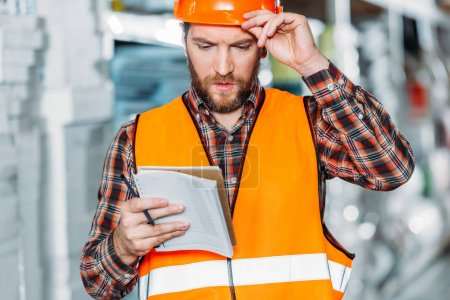 pensive worker in safety vest looking on notepad in storehouse