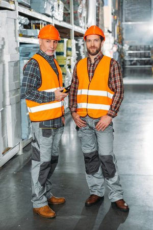 Photo pour Deux travailleurs masculins munis de talkie walkie en stock d'expédition - image libre de droit