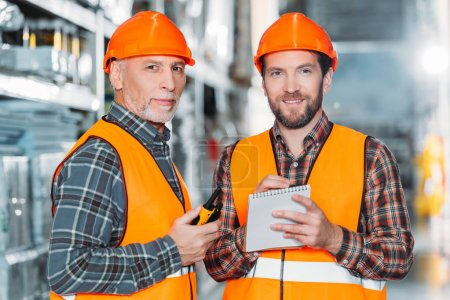 two male workers holding walkie talkie and notepad in storehouse
