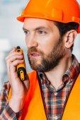 worker in helmet using walkie talkie