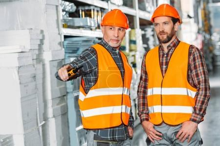 two male workers holding walkie talkie in storehouse
