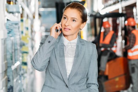 businesswoman talking on smartphone in shipping stock