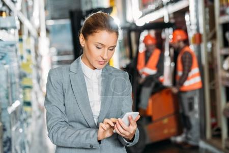 businesswoman using smartphone in shipping stock