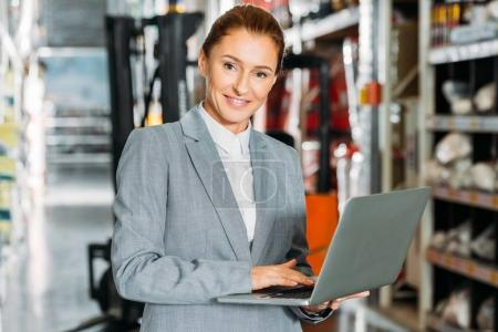 businesswoman using laptop in shipping stock