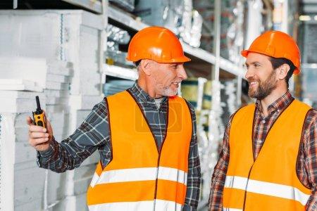 Foto de Dos trabajadores hombres de seguridad Chalecos y cascos con walkie talkie en almacén - Imagen libre de derechos