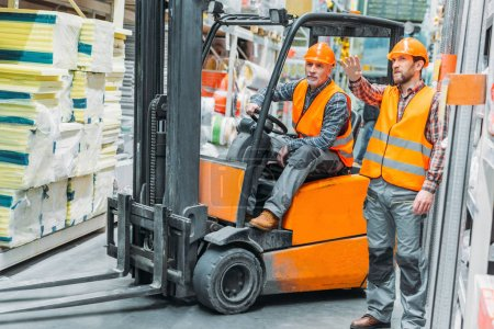 Photo for Worker and his senior colleague working with forklift machine in storage - Royalty Free Image