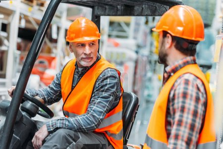 worker and his senior colleague working with forklift machine in shipping stock