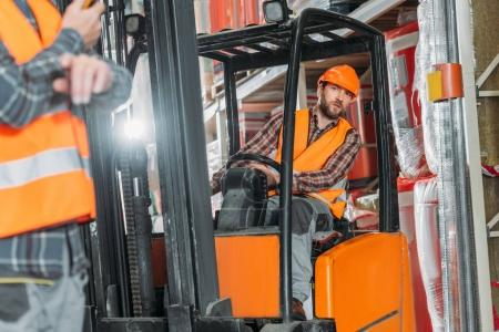 worker in safety vest and helmet sitting in forklift machine in storage