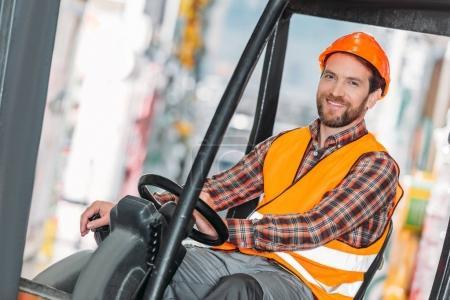 Foto de Trabajador de sexo masculino en chaleco y casco sentado en máquina elevadora en almacenamiento - Imagen libre de derechos
