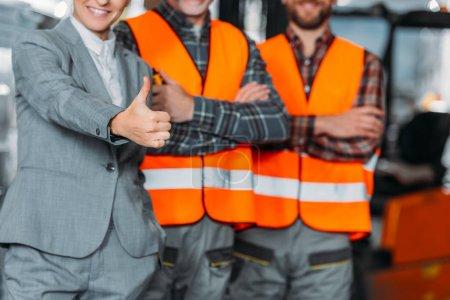 Photo pour Recadrée sur deux travailleurs et inspecteur montrant le pouce vers le haut - image libre de droit