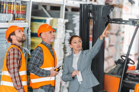Photo for Female inspector showing something to workers in storehouse - Royalty Free Image