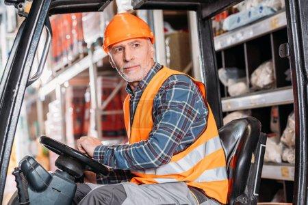 Foto de Trabajador Senior en seguridad chaleco y casco sentado en máquina elevadora en almacenamiento - Imagen libre de derechos