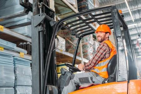 male worker in safety vest and helmet sitting in forklift machine in storage