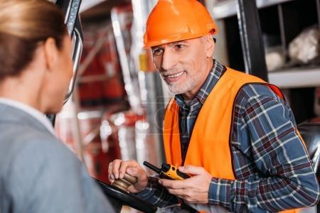 Foto de Trabajador Senior con walkie talkie sentado en máquina elevadora y hablando con la mujer empresaria en el almacenamiento - Imagen libre de derechos