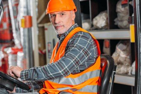 senior worker in safety vest and helmet sitting in forklift machine in storage