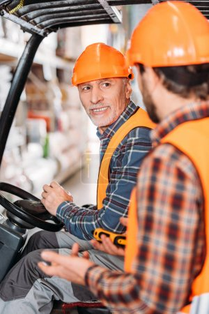 senior worker in safety vest and helmet sitting in forklift machine and talking with colleague in storage