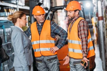 Photo for Male workers in safety vests and helmets talking with inspector in storehouse - Royalty Free Image