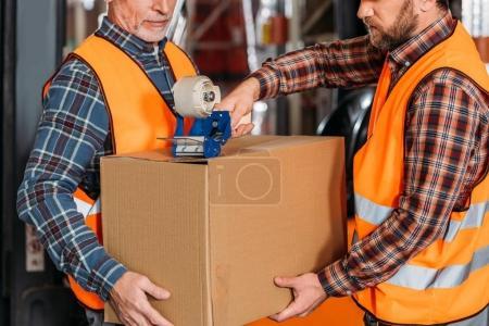 Photo pour Recadrée vue de travailleurs masculins en casque, une boîte en carton avec du Scotch d'emballage - image libre de droit