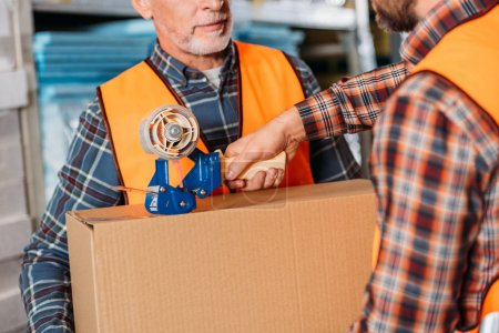 Photo for Cropped view of male workers in helmets packing cardboard box with scotch tape - Royalty Free Image