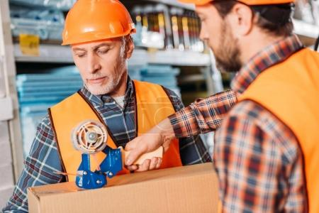 Foto de Trabajadores varones en chalecos de seguridad y cascos de embalaje caja de cartón con cinta scotch - Imagen libre de derechos