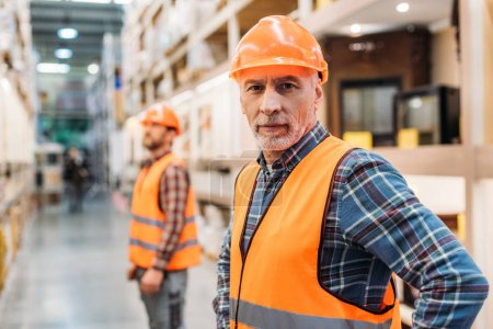 Foto de Trabajador Senior en seguridad chaleco y casco, compañero de trabajo de pie detrás en almacenamiento - Imagen libre de derechos