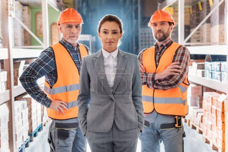 workers in helmets and inspector in suit posing in storehouse