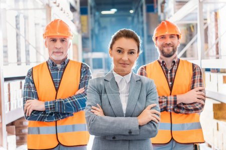 workers in helmets and inspector in suit posing with crossed arms in storage