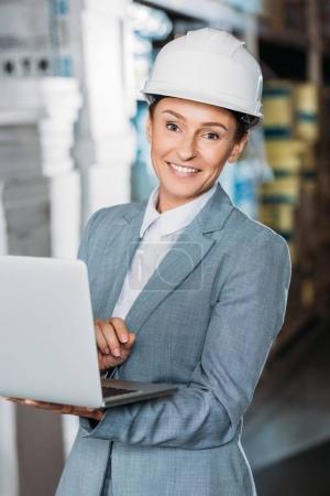 Foto de Mujer inspector de casco con laptop en almacén - Imagen libre de derechos