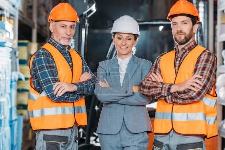 Photo for Workers in helmets and inspector in suit posing with crossed arms in storage - Royalty Free Image