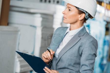 Photo pour Femme inspecteur en casque, écrire des notes dans le presse-papiers en entrepôt - image libre de droit
