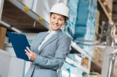female inspector in helmet writing notes on clipboard in warehouse