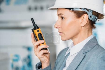 Photo pour Inspecteur féminin en casque avec talkie walkie en stock d'expédition - image libre de droit