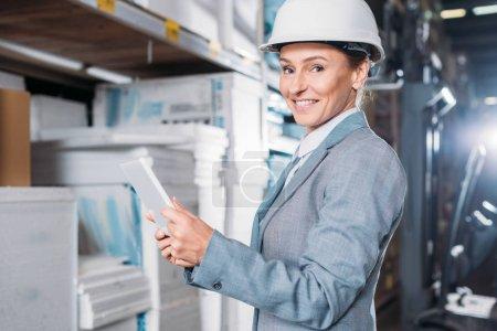 Photo pour Inspecteur de femelle dans le casque à l'aide de tablette numérique dans l'entrepôt - image libre de droit
